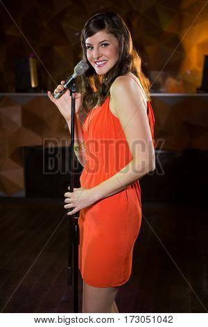 Portrait of beautiful woman singing in bar
