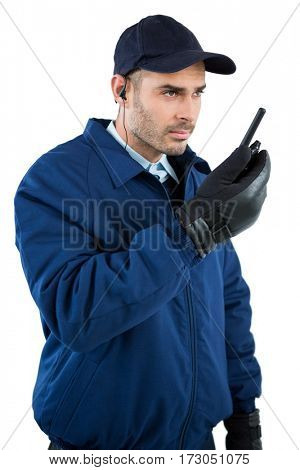Security officer talking on walkie-talkie against white background