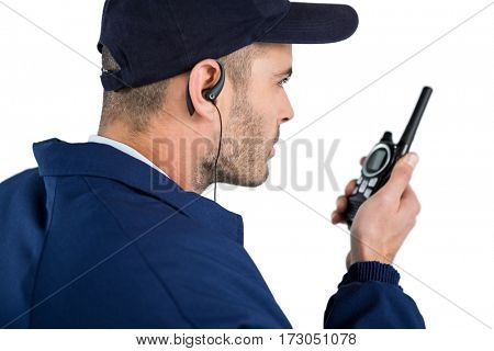 Close-up of security officer talking on walkie-talkie against white background