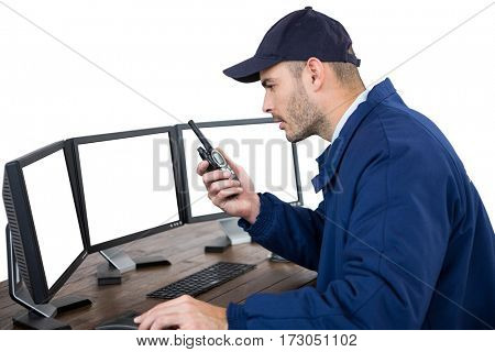 Concentrated security officer talking on walkie-talkie while looking at computer monitors