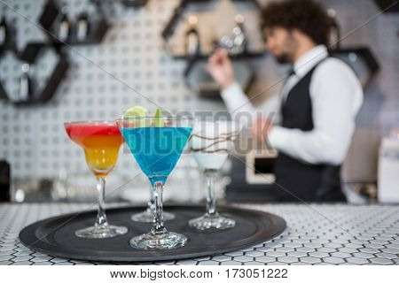 Various cocktails on a serving tray in bar counter and bartender standing in background