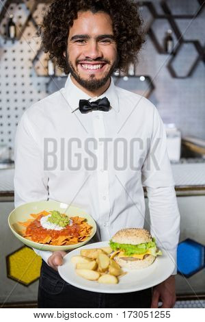 Portrait of smiling waiter holding plates of snacks and burger in bar
