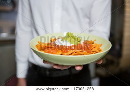 Mid section of waiter holding bowl of snacks in bar