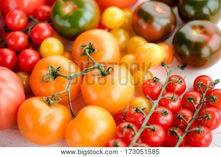 Close-up view of various fresh ripe tomatoes on wooden table