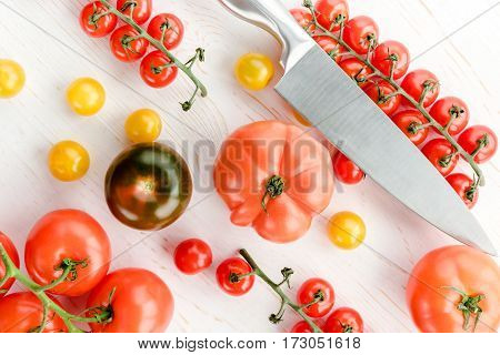 Close-up top view of various fresh tomatoes and kitchen knife on wooden table