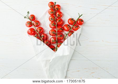 Top view of fresh ripe cherry tomatoes wrapped in white napkin
