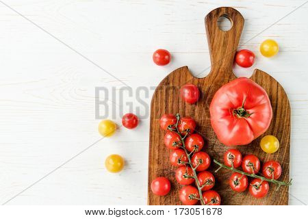Top view of fresh red and yellow tomatoes on cutting board on table