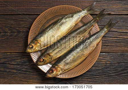 Smoked herring in plate on dark wooden table top view
