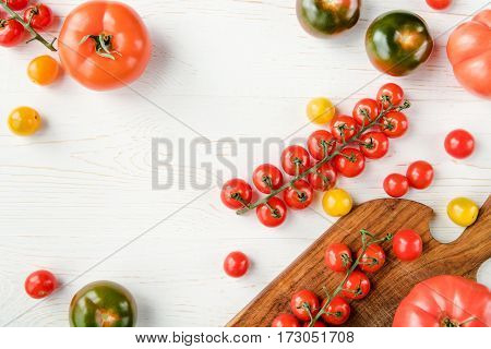 Top view of various fresh tomatoes on cutting board and wooden table