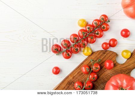 Top view of tasty fresh tomatoes on cutting board and wooden table