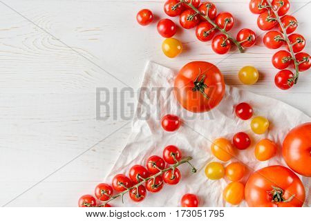 Top view of fresh ripe tomatoes on wooden table and white cloth