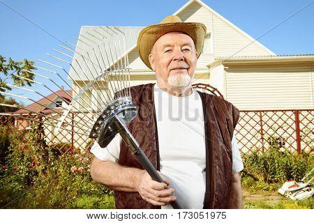 Raking in the garden. Happy senior man gardening in retirement.