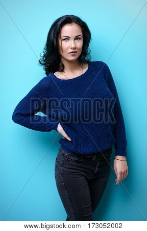 Portrait of a pretty young woman with brunette hair over blue background. Beauty, fashion concept. Cosmetics, make-up. Copy space.