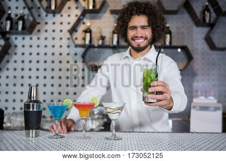 Portrait of bartender serving glass of gin at bar counter in bar