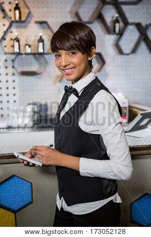 Portrait of bartender taking an order in a bar