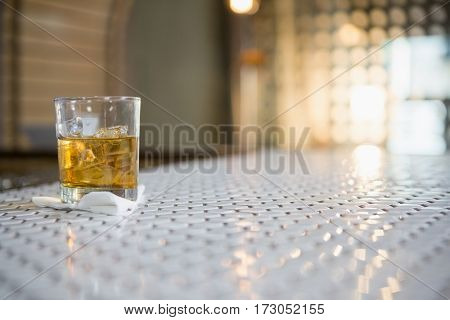 Glass of whisky with ice cube on bar counter at bar