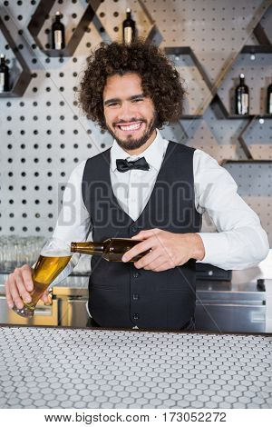 Portrait of smiling bartender pouring beer in glass at bar counter