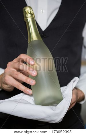 Mid section of bartender holding bottle of champagne in bar