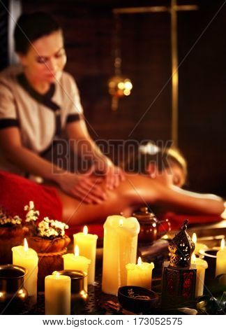 Massage of woman in spa salon. Girl on candles background treats problem back spa salon. Luxary interior with working masseuse . Shirodhara Pot background. Female bare back has relax .