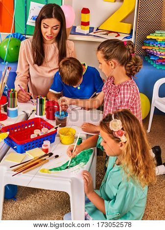 Children painting and drawing in kids club. Craft lesson in primary school. Kindergarten teacher and small students work together. Girl paints brush. Kid boy and girl coloring picture in class.