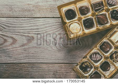 Assorted chocolate candies on a wooden background