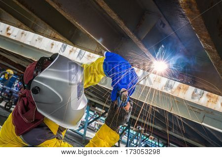 Worker repair the damage bottom side of container Industrial Worker at the factory welding closeup