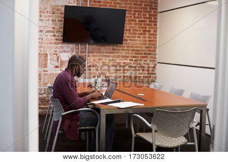 Businessman In Meeting Room Working On Laptop