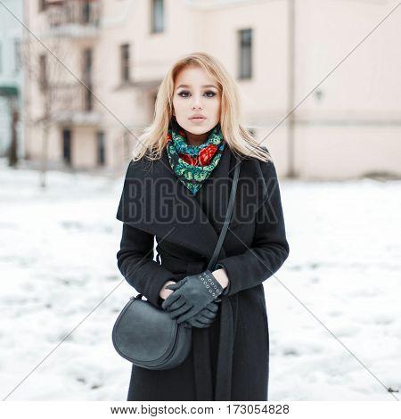 Beautiful Woman In A Black Coat With A Stylish Handbag Walking Near Buildings