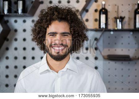 Portrait of smiling bartender standing in bar counter