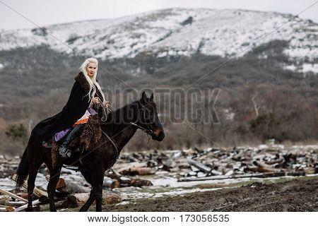 Beautiful Blonde Viking In A Black Cape On Horseback