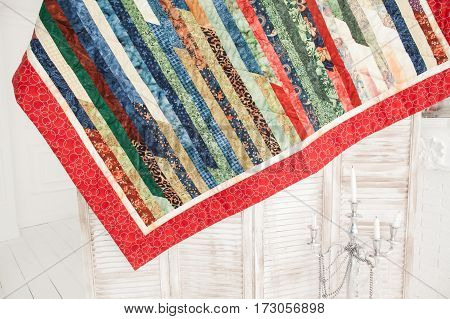 Patchwork quilt hangs on a wooden screen. Part of patchwork quilt on a white background.