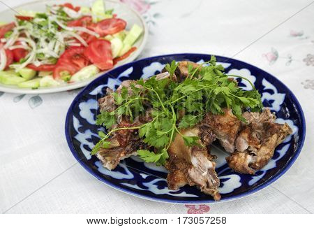 Traditional Uzbek grilled lamb meat with herbs and vegetables