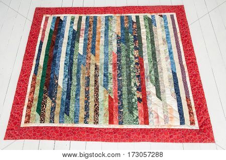 Patchwork quilt lies on a white wooden floor. Part of patchwork quilt on a white background.