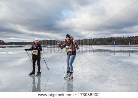 Two young woman ice skating together on wet ice.Upplands Vasby, Sweden - February 19, 2017: Two young cheerful woman skating on wet ice late winter day trying to avoid the deep water puddles on the ice. Participants of the annual ice skating event Vikinga