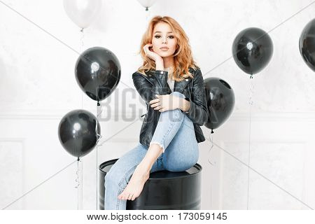 Beautiful Young Blonde Girl In A Black Leather Jacket And Blue Jeans Sits Near Balloons In The Studi