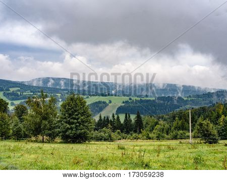 Natural cloudy misty landscape. mountain meadow and forests, both deciduous broadleaved and needle coniferous trees, electric overhead power line and horizon covered in clouds and mist, Czech republic, central Europe, Orlicke hory