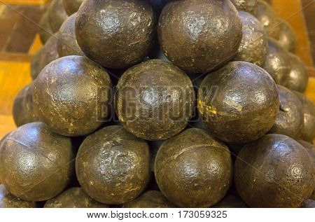 cannonball painted in dark paint piled in a pyramid style wallpaper background millitari