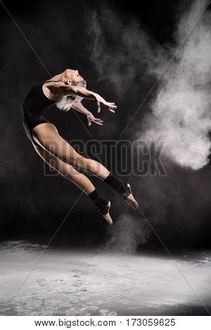 side view of woman in bodysuit with dust dancing on black