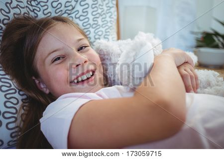 Portrait of happy girl lying with a teddy bear at home