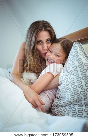 Mother kissing daughter on bed at home