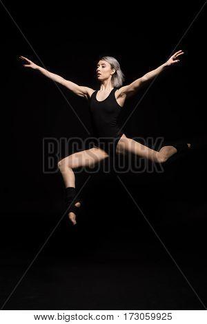 side view of focused jumping woman in bodysuit on black