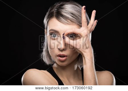portrait of shocked woman showing ok sign on black