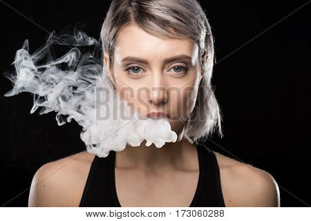Attractive young woman vaping and blowing smoke on black