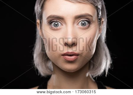 Close-up portrait of beautiful surprised young woman looking at camera