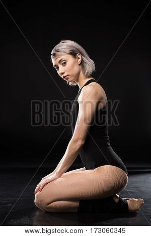 Attractive young woman contemporary dancer posing on black