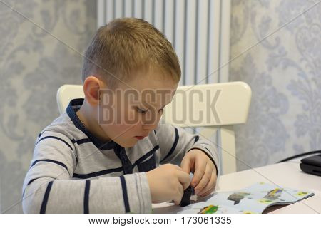 boy sitting at the table and creation toy according to the instructions
