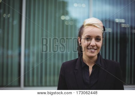 Close-up of smiling businesswoman standing in office campus