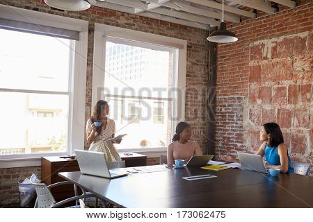 Group Of Businesswomen Working Together In Boardroom