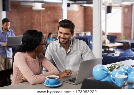Businessman And Businesswoman At Informal Meeting In Office