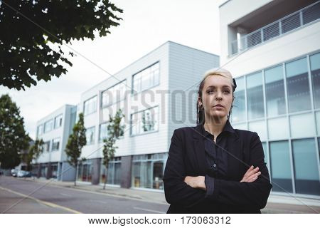 Thoughtful businesswoman standing with arms crossed in office campus